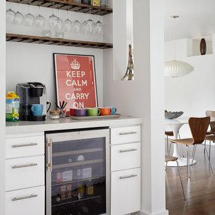 ニューヨークのコンテンポラリースタイルのおしゃれなホームバー (シンクなし、フラットパネル扉のキャビネット、白いキャビネット、濃色無垢フローリング) の写真