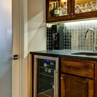 Idee per un piccolo angolo bar con lavandino minimal con lavello sottopiano, ante in stile shaker, ante in legno scuro, top in saponaria, paraspruzzi con piastrelle di metallo e pavimento in legno massello medio