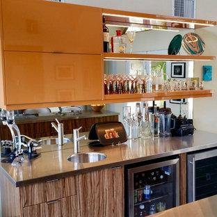 Ispirazione per un angolo bar con lavandino minimalista di medie dimensioni con lavello integrato, ante lisce, ante arancioni, top in acciaio inossidabile e paraspruzzi a specchio