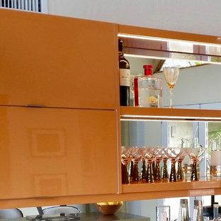 他の地域の中くらいのミッドセンチュリースタイルのおしゃれな着席型バー (I型、フラットパネル扉のキャビネット、オレンジのキャビネット、ミラータイルのキッチンパネル) の写真