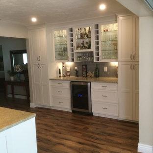 Exemple d'un bar de salon linéaire chic de taille moyenne avec un placard à porte shaker, des portes de placard blanches, un plan de travail en granite, une crédence grise, une crédence en carrelage métro et un sol en bois brun.