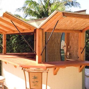 Immagine di un piccolo bancone bar tropicale con top in legno, paraspruzzi marrone, paraspruzzi in legno, pavimento in cemento e pavimento grigio