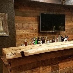 デンバーの広いラスティックスタイルのおしゃれな着席型バー (L型、アンダーカウンターシンク、落し込みパネル扉のキャビネット、濃色木目調キャビネット、木材カウンター、茶色いキッチンパネル、木材のキッチンパネル、ラミネートの床、茶色い床) の写真