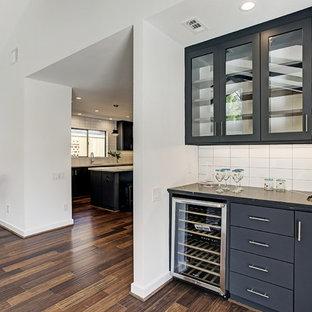 ヒューストンのミッドセンチュリースタイルのおしゃれなウェット バー (I型、アンダーカウンターシンク、フラットパネル扉のキャビネット、黒いキャビネット、クオーツストーンカウンター、白いキッチンパネル、セラミックタイルのキッチンパネル、竹フローリング、茶色い床、黒いキッチンカウンター) の写真