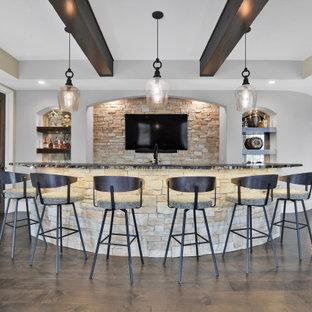 カンザスシティの広いトランジショナルスタイルのおしゃれな着席型バー (ll型、茶色いキッチンパネル、石タイルのキッチンパネル、無垢フローリング、茶色い床、黒いキッチンカウンター) の写真