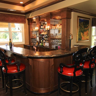 Inspiration for a large country l-shaped medium tone wood floor seated home bar remodel in Sacramento with an undermount sink, furniture-like cabinets, dark wood cabinets, granite countertops and multicolored backsplash
