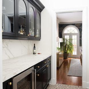 Idee per un angolo bar con lavandino classico di medie dimensioni con ante nere, ante con bugna sagomata, top in marmo, paraspruzzi bianco, paraspruzzi in marmo, pavimento con piastrelle in ceramica, pavimento beige e top bianco