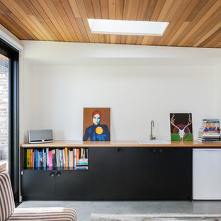 Small contemporary single-wall wet bar in Sydney with a drop-in sink, flat-panel cabinets, black cabinets, wood benchtops, concrete floors, grey floor and beige benchtop.