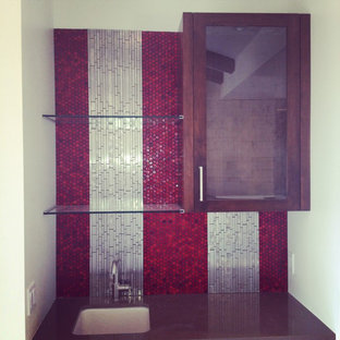 This is an example of a small contemporary single-wall wet bar in San Diego with a submerged sink, glass-front cabinets, dark wood cabinets, composite countertops, multi-coloured splashback, mosaic tiled splashback and grey worktops.