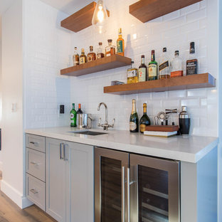 This is an example of a small traditional single-wall wet bar in Los Angeles with a submerged sink, shaker cabinets, grey cabinets, engineered stone countertops, white splashback, metro tiled splashback, light hardwood flooring, beige floors and white worktops.