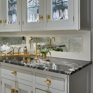 Mid-sized transitional single-wall porcelain floor and multicolored floor wet bar photo in Chicago with an undermount sink, recessed-panel cabinets, white cabinets and marble countertops