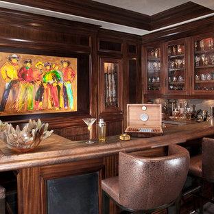 Idées déco pour un bar de salon classique en U de taille moyenne avec des tabourets, un évier posé, un placard à porte vitrée, des portes de placard en bois brun, un plan de travail en bois, une crédence beige, une crédence en dalle de pierre et un sol en bois foncé.