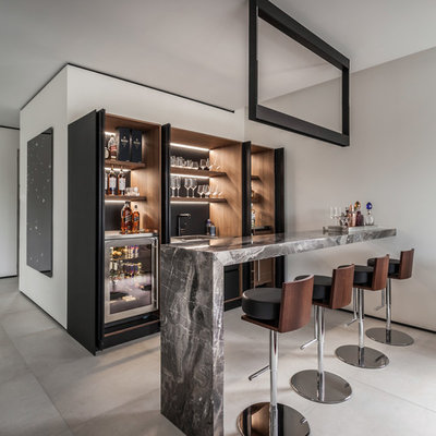 Inspiration for a large contemporary galley porcelain tile and gray floor wet bar remodel in Miami with dark wood cabinets, marble countertops, a drop-in sink, black backsplash, gray countertops and open cabinets