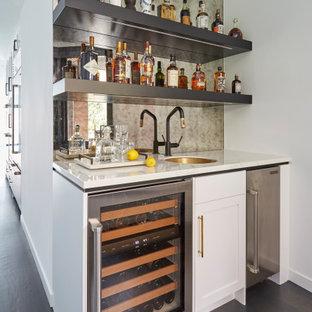 Cette image montre un bar de salon avec évier linéaire design avec un évier encastré, un placard à porte shaker, des portes de placard blanches, une crédence en carreau de miroir, un sol en bois foncé, un sol marron et un plan de travail blanc.