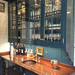 シンシナティの中くらいのトラディショナルスタイルのおしゃれなウェット バー (I型、アンダーカウンターシンク、ガラス扉のキャビネット、青いキャビネット、木材カウンター、青いキッチンパネル、濃色無垢フローリング、茶色いキッチンカウンター) の写真