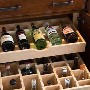 Idee per un grande armadio bar classico con ante con bugna sagomata, ante in legno bruno, top in granito, paraspruzzi a specchio, lavello da incasso, pavimento marrone e top nero