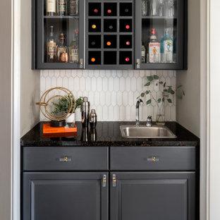 Immagine di un angolo bar con lavandino chic con ante nere, top in granito, paraspruzzi con piastrelle in ceramica e top nero
