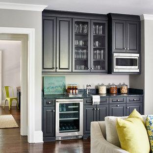 Immagine di un angolo bar con lavandino tradizionale con lavello sottopiano, ante con bugna sagomata, ante nere e pavimento in legno massello medio