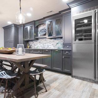 フィラデルフィアの巨大なカントリー風おしゃれなウェット バー (I型、アンダーカウンターシンク、レイズドパネル扉のキャビネット、グレーのキャビネット、クオーツストーンカウンター、マルチカラーのキッチンパネル、ガラスタイルのキッチンパネル、ラミネートの床、ベージュの床、グレーのキッチンカウンター) の写真