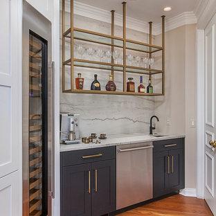 デトロイトの中くらいのトランジショナルスタイルのおしゃれなウェット バー (I型、アンダーカウンターシンク、シェーカースタイル扉のキャビネット、黒いキャビネット、珪岩カウンター、白いキッチンパネル、無垢フローリング、茶色い床、白いキッチンカウンター) の写真