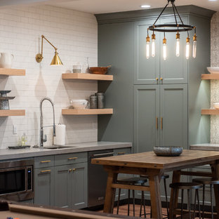 Example of a country l-shaped medium tone wood floor and brown floor seated home bar design in Salt Lake City with an undermount sink, shaker cabinets, green cabinets, white backsplash, subway tile backsplash and gray countertops