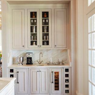 Modelo de bar en casa tradicional, grande, con armarios con rebordes decorativos, puertas de armario blancas, encimera de mármol, suelo de madera oscura, salpicadero blanco, salpicadero de losas de piedra y fregadero bajoencimera