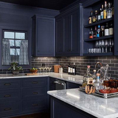 Example of a mid-sized beach style u-shaped dark wood floor and brown floor wet bar design in Dallas with shaker cabinets, blue cabinets, black backsplash, subway tile backsplash, an undermount sink, marble countertops and gray countertops