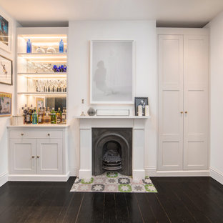 Small traditional single-wall home bar in London with no sink, shaker cabinets, grey cabinets, mirror splashback, dark hardwood flooring and grey worktops.