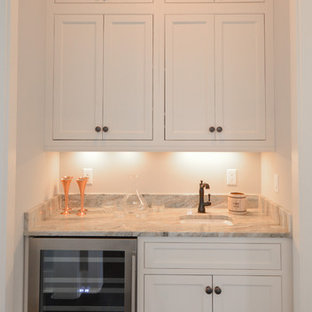 Photo of a small traditional single-wall wet bar in Atlanta with a submerged sink, shaker cabinets, white cabinets, marble worktops and brown floors.