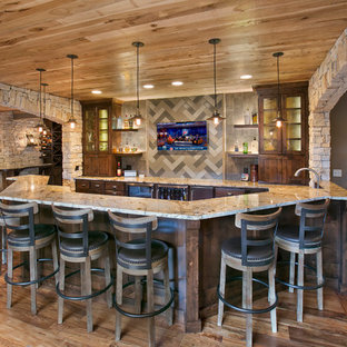 Inspiration for a rustic u-shaped medium tone wood floor home bar remodel in Minneapolis with raised-panel cabinets, dark wood cabinets and gray backsplash