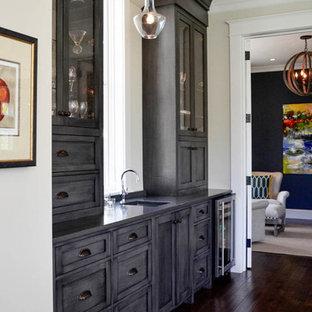 Foto de bar en casa con fregadero lineal, clásico renovado, con fregadero bajoencimera, armarios con paneles lisos, puertas de armario grises, suelo de madera oscura y suelo marrón