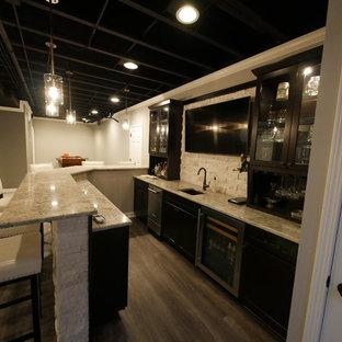 シカゴの中くらいのトランジショナルスタイルのおしゃれな着席型バー (L型、アンダーカウンターシンク、ガラス扉のキャビネット、黒いキャビネット、御影石カウンター、白いキッチンパネル、石タイルのキッチンパネル、ラミネートの床、グレーの床、ベージュのキッチンカウンター) の写真