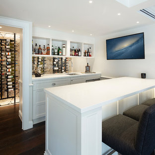 Design ideas for a mid-sized beach style seated home bar in Brisbane with an undermount sink, white cabinets, quartz benchtops, dark hardwood floors, brown floor, white benchtop, open cabinets and glass sheet splashback.