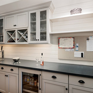 Home bar - mid-sized farmhouse l-shaped medium tone wood floor and brown floor home bar idea in Charlotte with no sink, recessed-panel cabinets, gray cabinets, quartz countertops, white backsplash, wood backsplash and black countertops