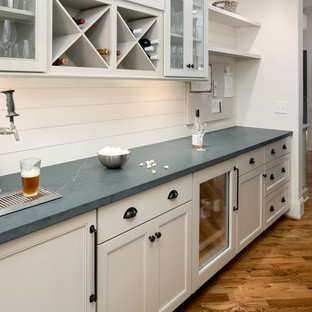 Inspiration for a mid-sized cottage l-shaped medium tone wood floor and brown floor home bar remodel in Charlotte with no sink, recessed-panel cabinets, gray cabinets, quartz countertops, white backsplash, wood backsplash and black countertops