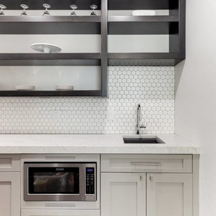 This is an example of a small traditional single-wall wet bar in Salt Lake City with a submerged sink, recessed-panel cabinets, grey cabinets, marble worktops, white splashback, ceramic splashback, light hardwood flooring, beige floors and grey worktops.