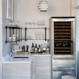 Foto di un armadio bar minimal di medie dimensioni con ante lisce, ante grigie, paraspruzzi bianco, paraspruzzi in lastra di pietra, lavello sottopiano, parquet scuro, pavimento marrone e top bianco