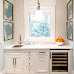 Foto di un ampio angolo bar tropicale con lavello sottopiano, ante bianche, top in granito, paraspruzzi bianco, ante con riquadro incassato, parquet chiaro e pavimento marrone