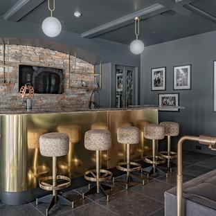 Ejemplo de bar en casa con barra de bar clásico renovado con armarios con paneles con relieve, puertas de armario grises, salpicadero multicolor, salpicadero de azulejos de piedra y suelo negro