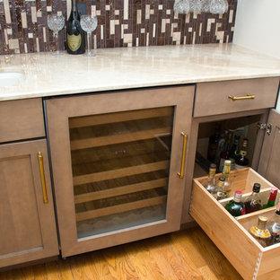 ヒューストンの小さいコンテンポラリースタイルのおしゃれなウェット バー (I型、アンダーカウンターシンク、シェーカースタイル扉のキャビネット、ベージュのキャビネット、大理石カウンター、茶色いキッチンパネル、ガラスタイルのキッチンパネル、淡色無垢フローリング、茶色い床) の写真