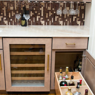 Photo of a small contemporary single-wall wet bar in Houston with a submerged sink, shaker cabinets, beige cabinets, marble worktops, brown splashback, glass tiled splashback, light hardwood flooring and brown floors.