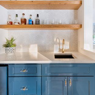 Foto di un angolo bar design di medie dimensioni con lavello sottopiano, ante in stile shaker, ante blu, top in quarzo composito, paraspruzzi grigio, paraspruzzi con piastrelle di cemento, parquet chiaro e top bianco