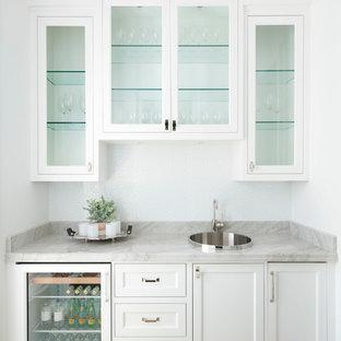 Ispirazione per un angolo bar con lavandino mediterraneo con parquet chiaro, lavello da incasso, ante di vetro, ante bianche, pavimento beige e top grigio