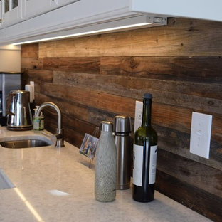 Inspiration for a small rustic single-wall carpeted and beige floor wet bar remodel in Denver with an undermount sink, raised-panel cabinets, white cabinets, granite countertops, brown backsplash and wood backsplash