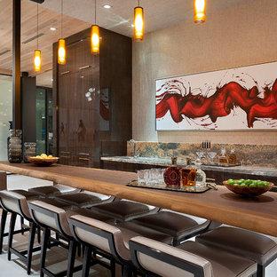 Immagine di un bancone bar design con lavello sottopiano, ante lisce, ante in legno bruno e pavimento grigio