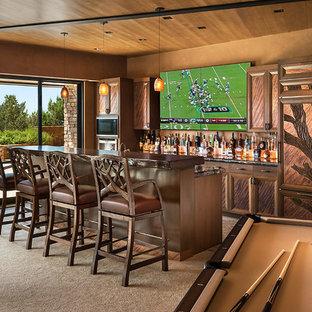 Idee per un grande bancone bar american style con consolle stile comò, moquette, lavello sottopiano, top in legno, paraspruzzi in lastra di pietra, ante in legno scuro e top marrone
