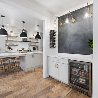 他の地域のトランジショナルスタイルのおしゃれなドライ バー (I型、シェーカースタイル扉のキャビネット、グレーのキャビネット、白いキッチンカウンター、シンクなし、黒いキッチンパネル、茶色い床) の写真