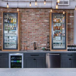 Idées déco pour un grand bar de salon avec évier industriel avec un plan de travail en béton, une crédence en brique, un plan de travail gris, un évier encastré, un placard avec porte à panneau encastré, des portes de placard grises et une crédence rouge.