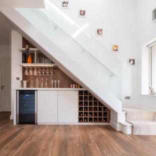 Ispirazione per un angolo bar senza lavandino minimal di medie dimensioni con ante lisce, ante bianche, paraspruzzi marrone, pavimento in legno massello medio, pavimento marrone e top bianco