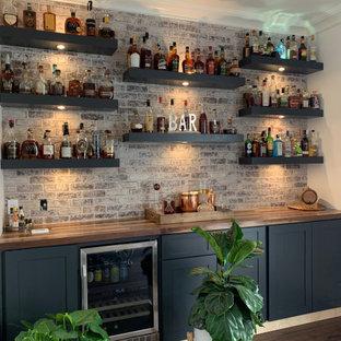 Idee per un piccolo angolo bar senza lavandino chic con ante lisce, top in legno, paraspruzzi in mattoni e pavimento in legno massello medio